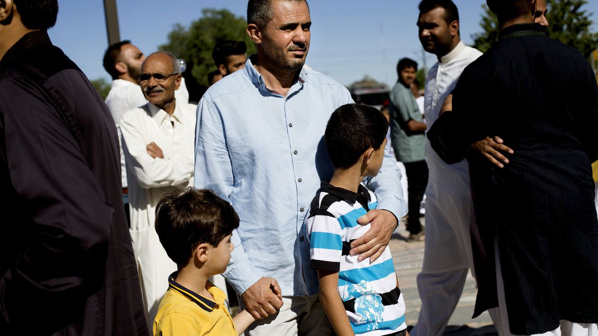 Malek Hamad holds his sons Eslam and Abdullah while searching for his wife's cousin, after praying at the end of Ramadan, at the Khadeeja Islamic Center in West Valley City, June 25, 2017. The Hamads had been in the United States for only a month as of th