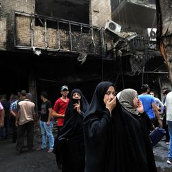 Iraqi women wait to hear about family members who went missing after a car bomb hit Karada, a busy shopping district in the center of Baghdad, Iraq, Sunday, July 3, 2016. Dozens of people have been killed and more than 100 wounded in two separate bomb attacks in the Iraqi capital Sunday morning, Iraqi officials said.