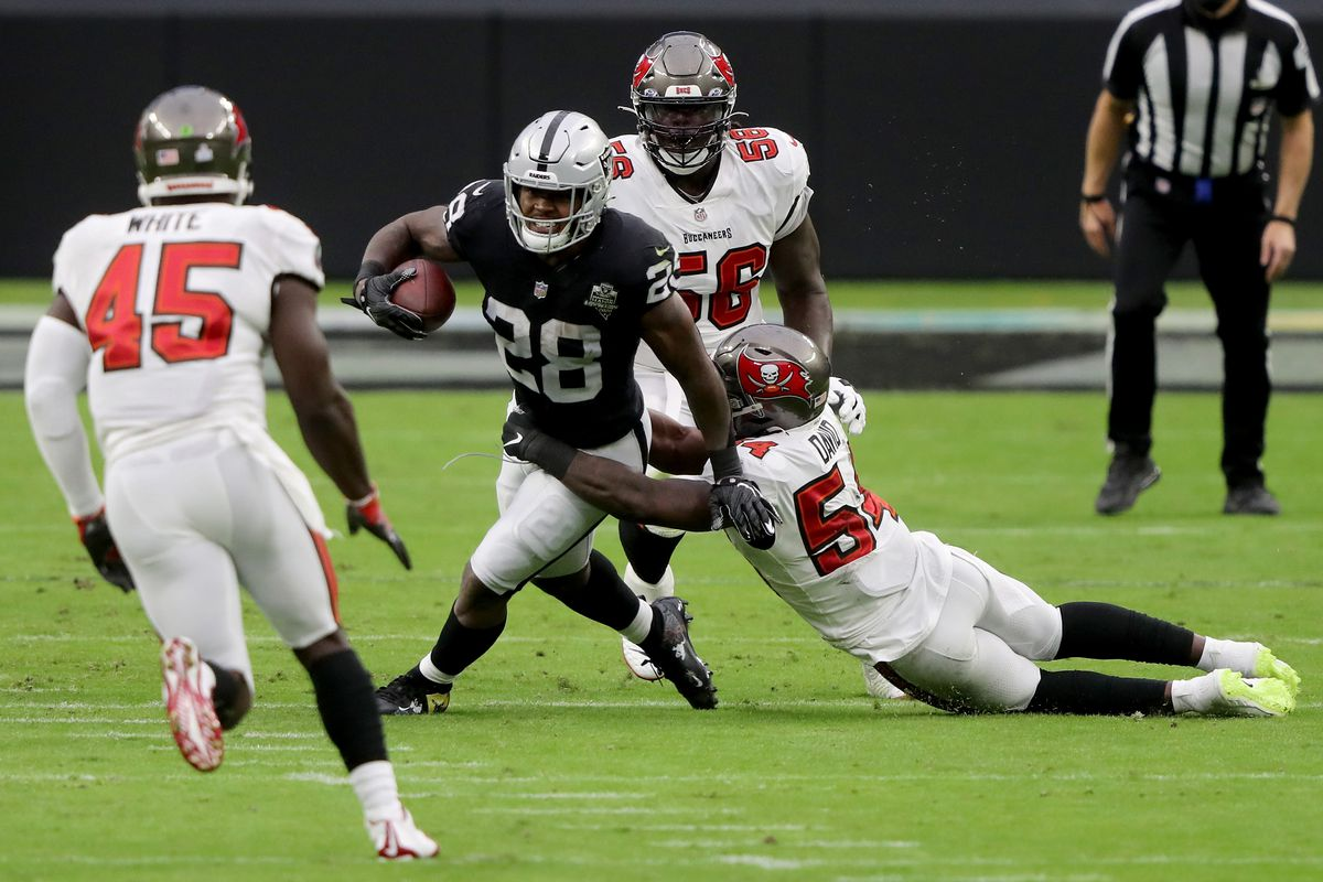 Josh Jacobs #28 of the Las Vegas Raiders runs with the ball while being tackled by Lavonte David #54 of the Tampa Bay Buccaneers in the first quarter at Allegiant Stadium on October 25, 2020 in Las Vegas, Nevada.