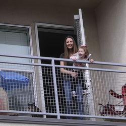Whitney Beaslin and daughter Charlotte pose for a photo on the deck of their apartment in Sandy on Wednesday, April 1, 2020.Beaslin, a server and a single mom, is worried about getting evicted due to losing work from the COVID-19 pandemic.
