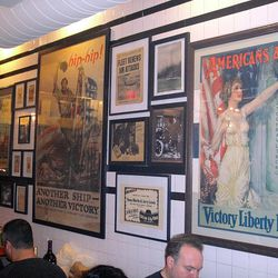 The wall is covered in period ads and military victory announcements.