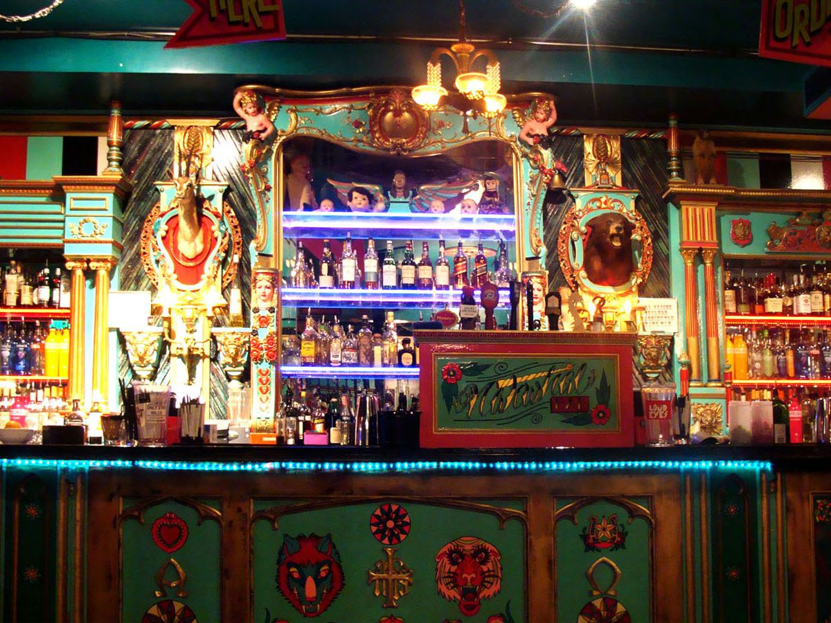 The ornate bar at Unicorn's downstairs Narwhal Bar area, with taxidermy and bottles of liquors displayed.