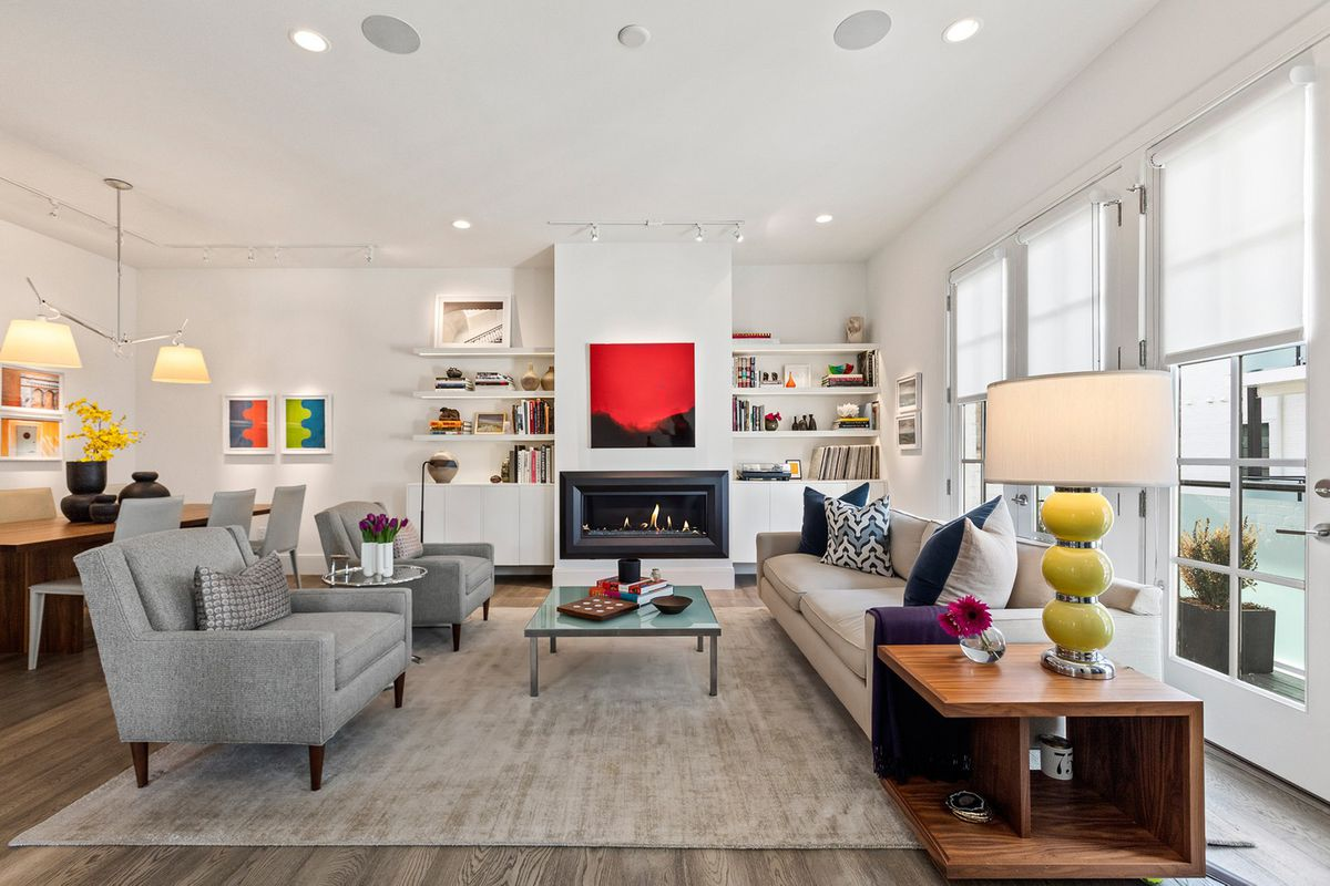 A large white living room in a townhome with a red painting on the wall.