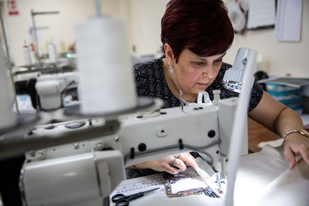 A woman sits and sews at an industrial sewing machine