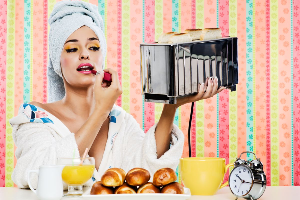 A photo collage of a woman in a bathrobe applying lipstick in the reflection of a toaster