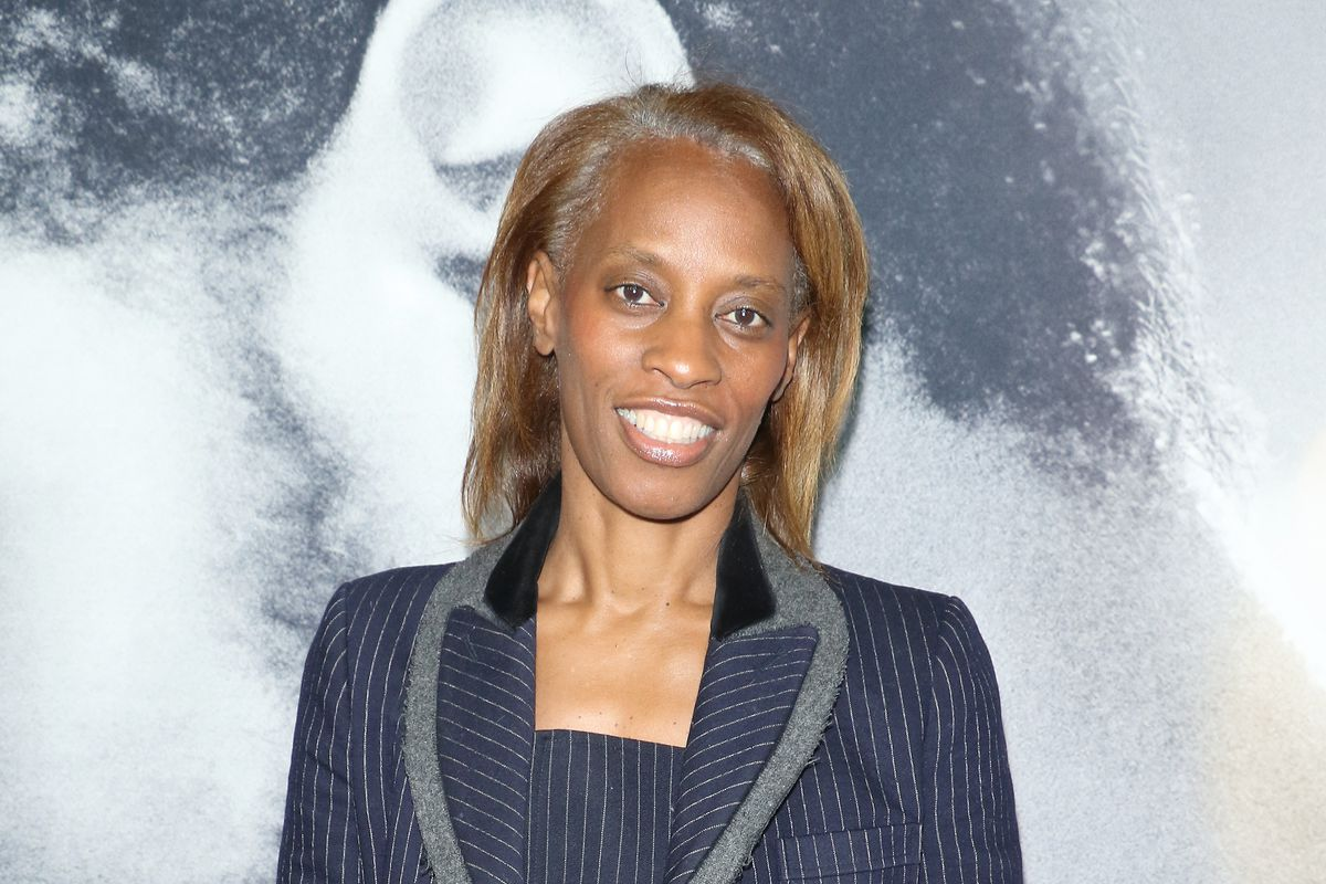 Dawn Davis, in a navy pinstripe suit, stands in front of a a large movie poster featuring LaKeith Stanfield's ear