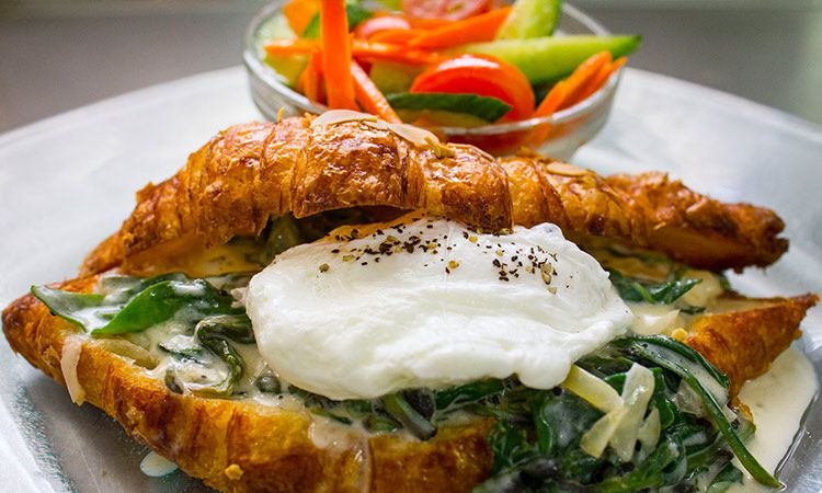 A lump of fresh gooey cheese sits in a sliced croissant on a bed of cooked greens with a small dish of sliced vegetables beyond it on a plate