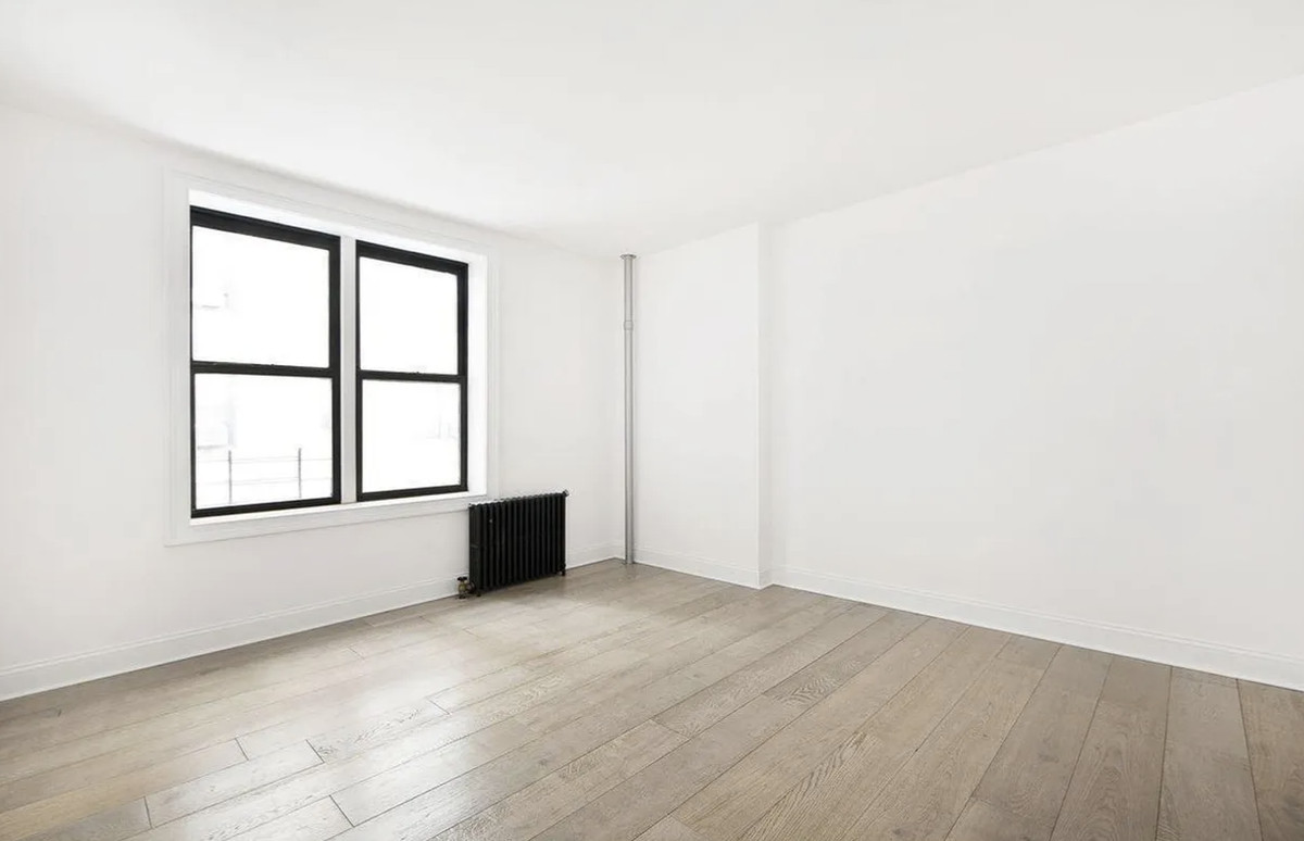 A bedroom with hardwood floors, white walls, and two windows.