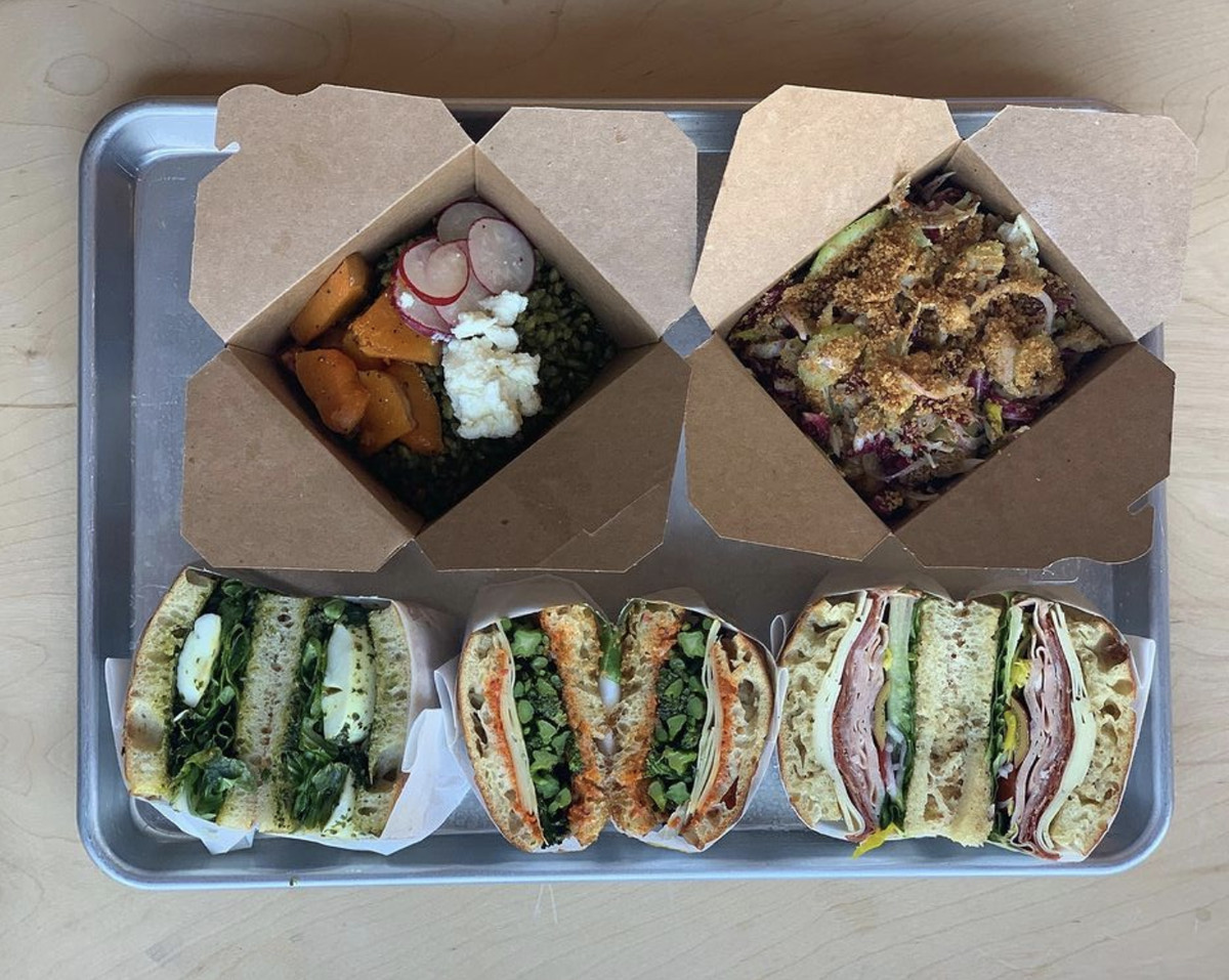 An overhead photograph of three sandwiches that have been cut in half and two salads in cardboard takeout containers