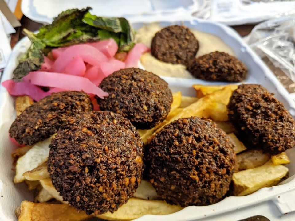 A white styrofoam container of falafel, fries, and pickled onions