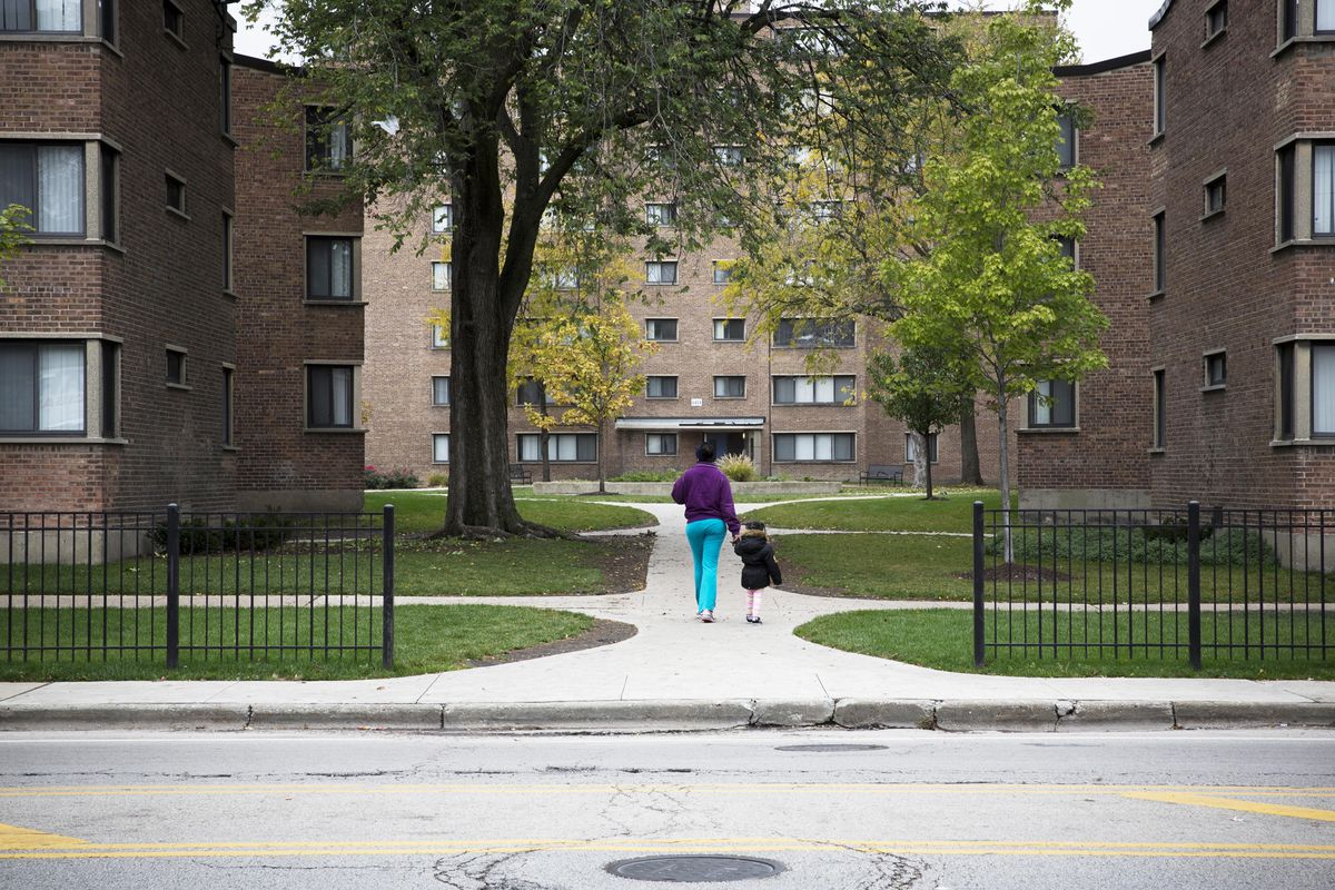 A mother walks with a young child into the Parkway Garden Apartment complex in the 6400 block of Martin Luther King Drive in Chicago's Woodlawn neighborhood.