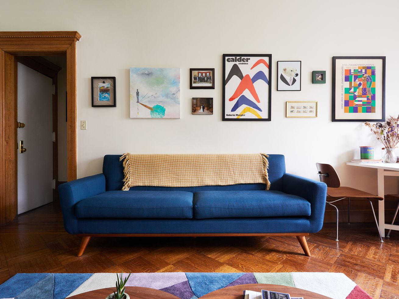 A living room with a blue midcentury-style couch in the center. A colorful geometric rug sits afoot, above herringbone floors. Various artworks hang on white walls.