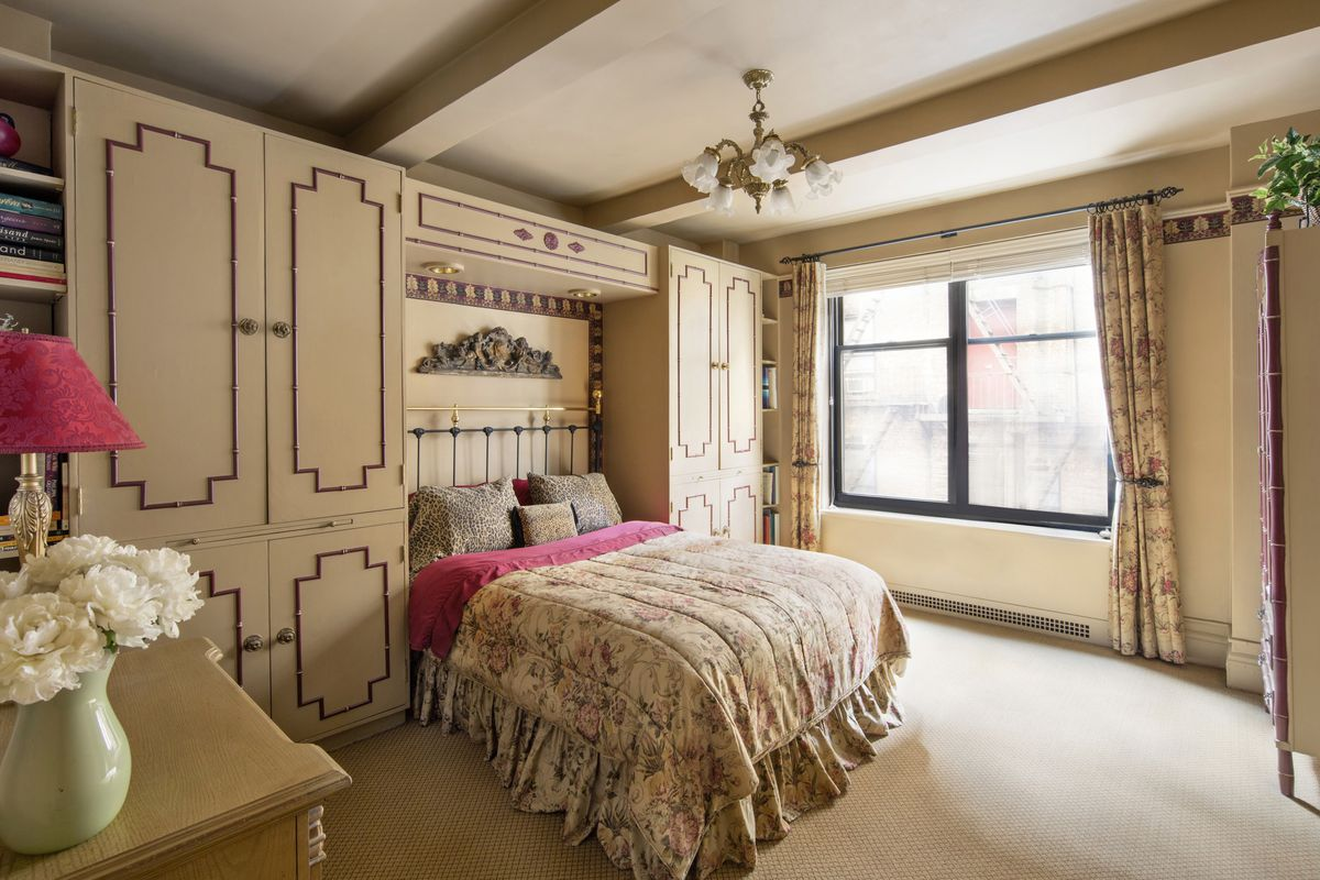 A bedroom with a medium-sized bed, beige built-in cabinets, and a large window.