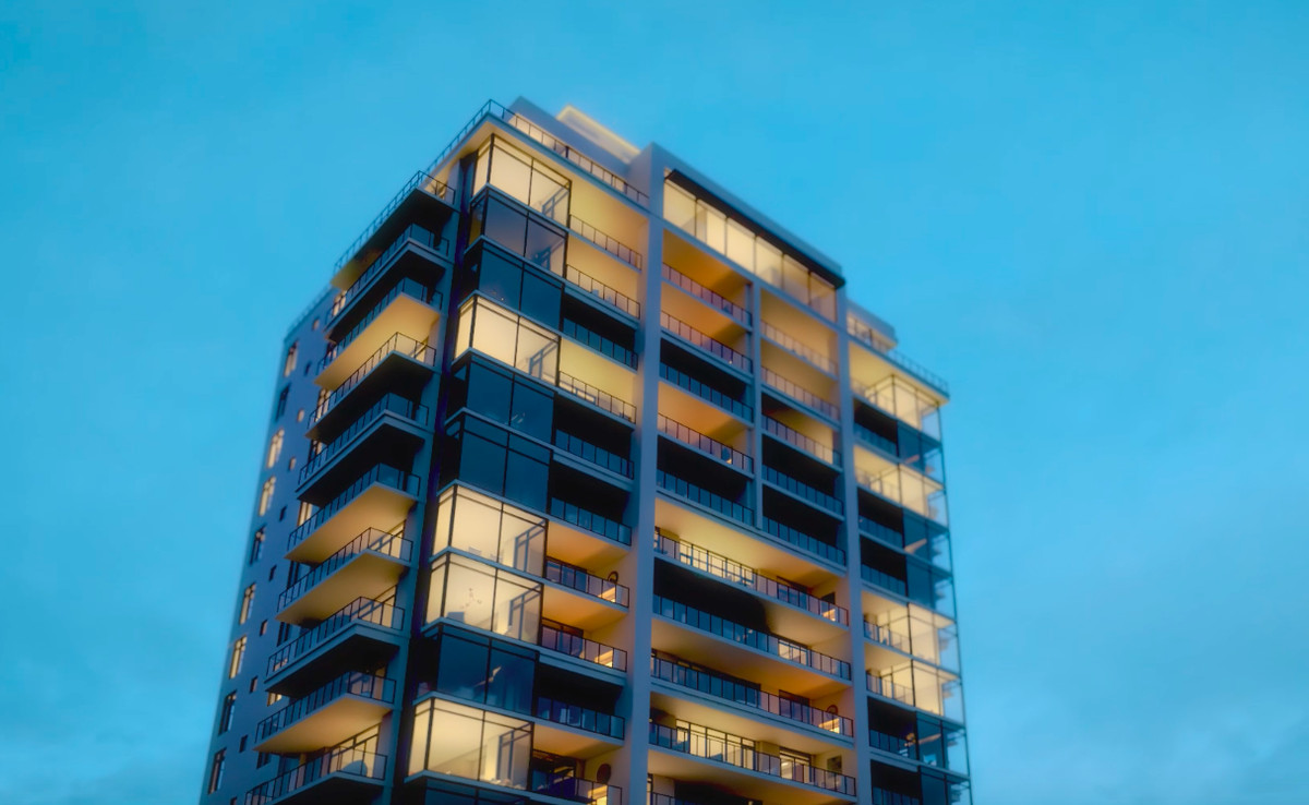 A condo tower shown at evening against a blue sky.