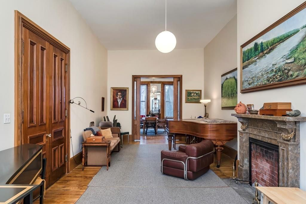 A long, high-ceilinged living room with a marble fireplace and a piano and other furniture.