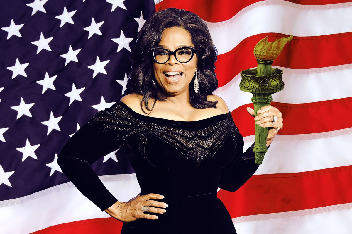 Oprah smiling and holding the Statue of Liberty's torch in front of an American flag