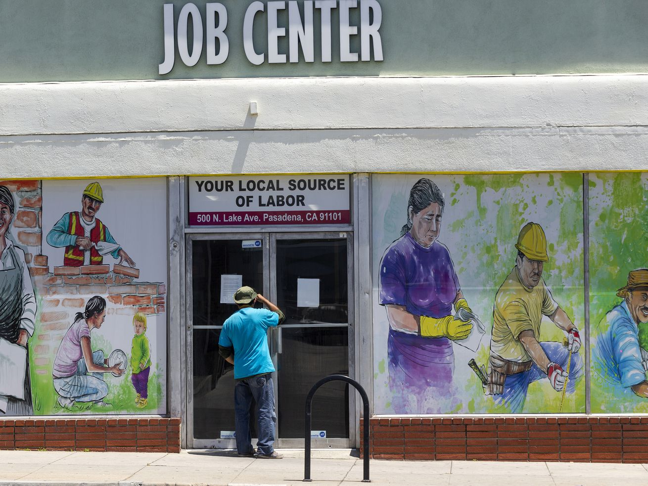 In this May 7, 2020, file photo, a person looks inside the closed doors of the Pasadena Community Job Center in Pasadena, Calif., during the coronavirus outbreak.