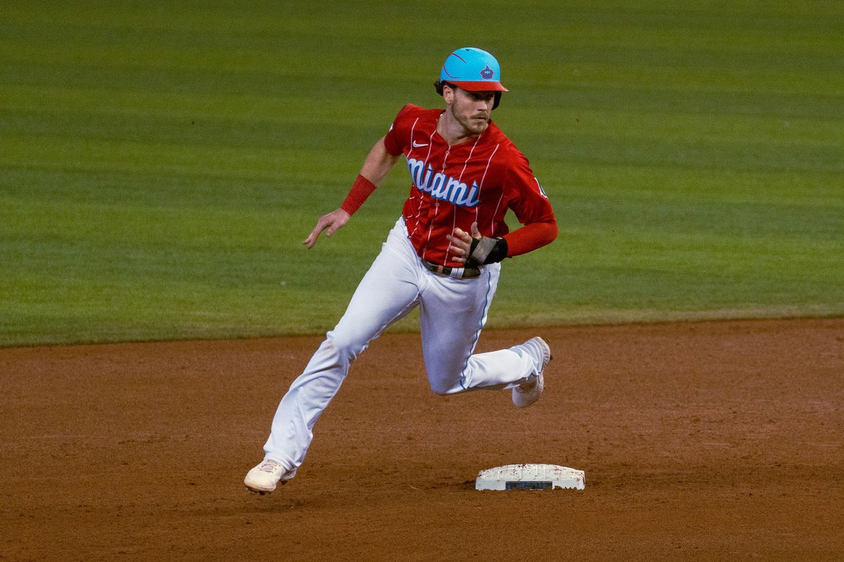 Brian Anderson rounding second base in the Marlins Legacy Red City Connect uniform
