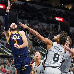 Utah Jazz's Ricky Rubio, left, shoots as San Antonio Spurs' Patty Mills defends during the second half of an NBA basketball game Saturday, Feb. 3, 2018, in San Antonio. Utah won 120-111. (AP Photo/Darren Abate)
