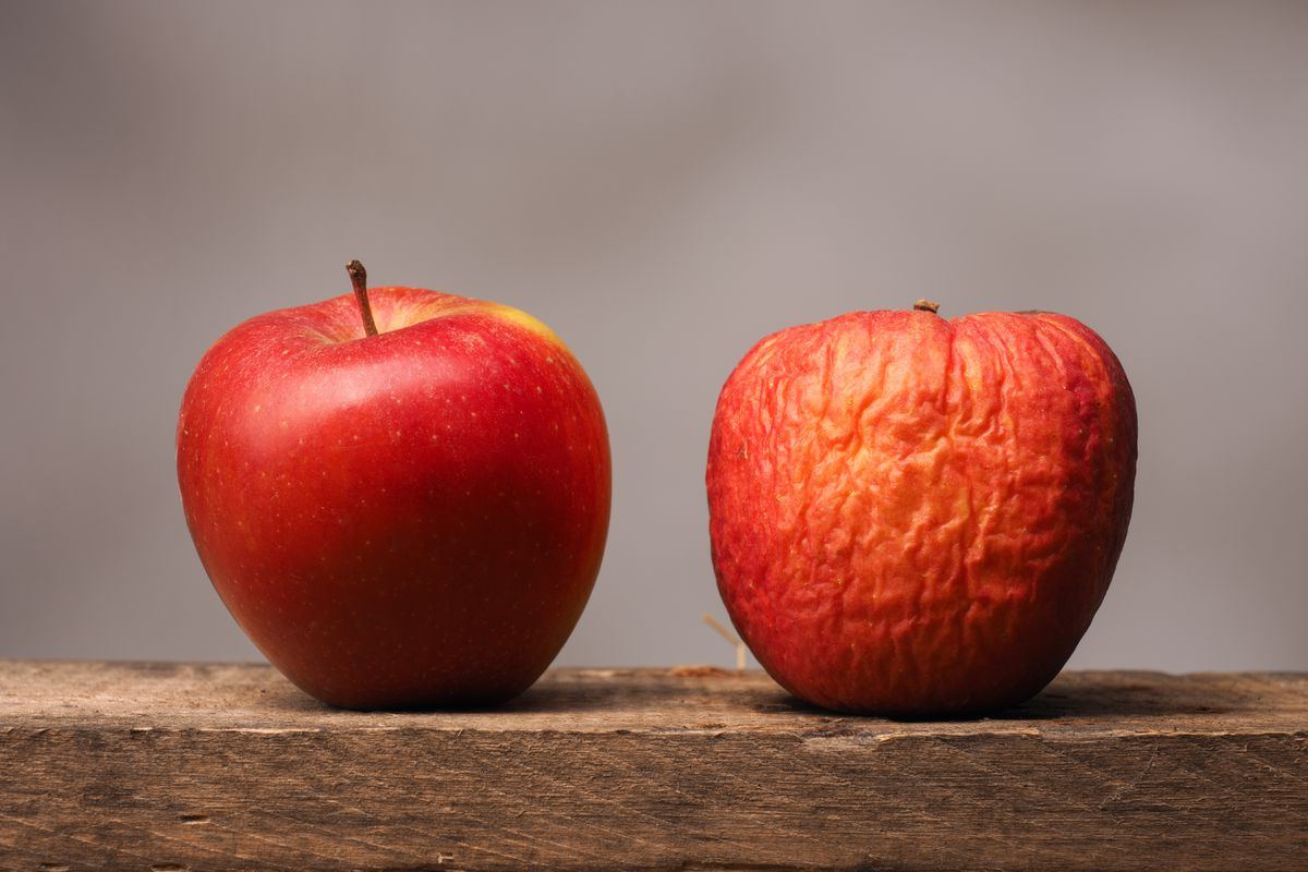 Two apples on a board, one fresh and one old and wrinkled.