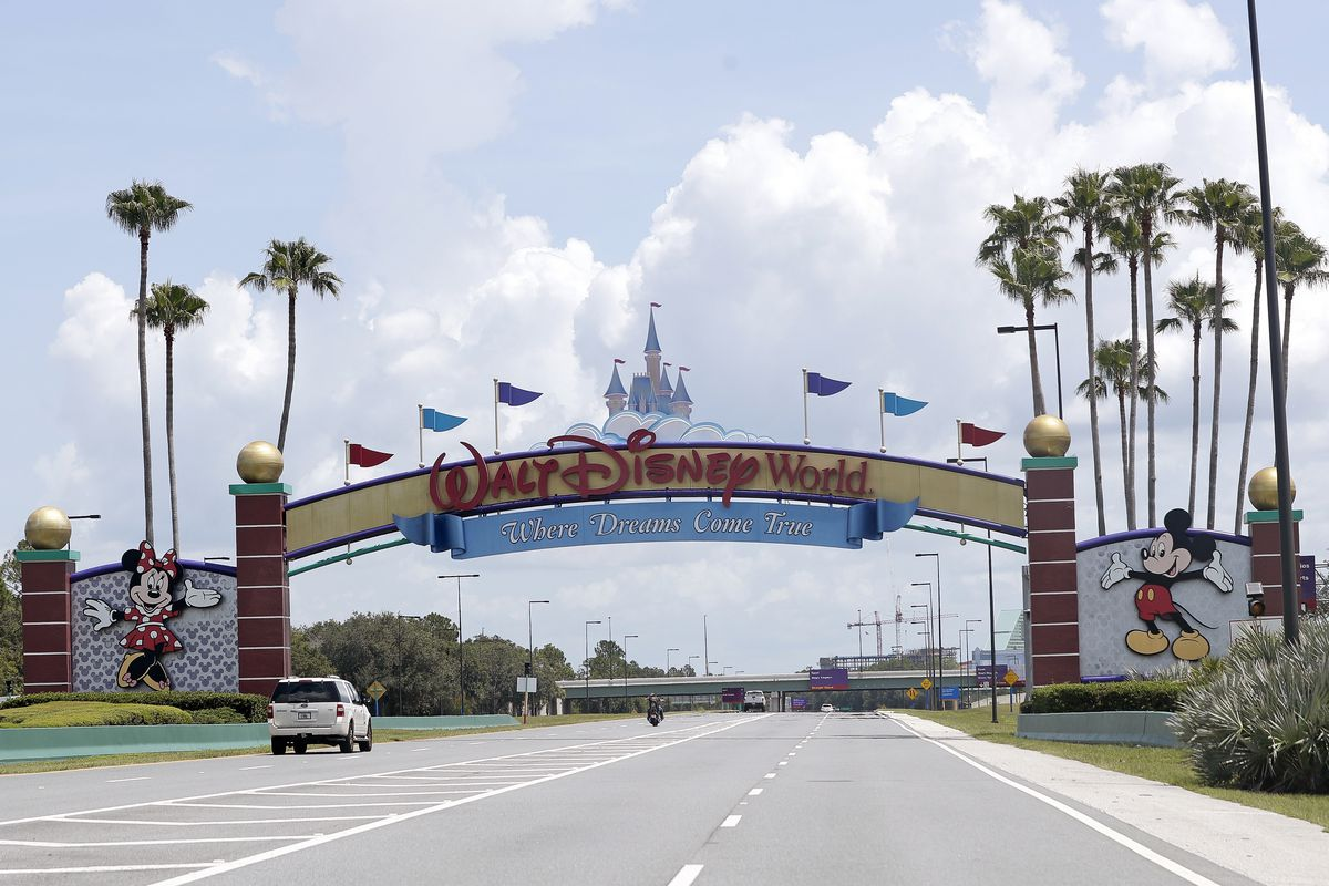 Cars drive under a sign greeting visitors near the entrance to Walt Disney World, in Lake Buena Vista, Fla.