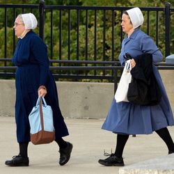 Two Amish women walk to the U.S. Federal Courthouse in Cleveland on Thursday, Sept. 20, 2012.  The jury will begin their fifth day of deliberations in the trial of 16 Amish people accused of hate crimes in hair- and beard-cutting attacks against fellow Amish in Ohio.