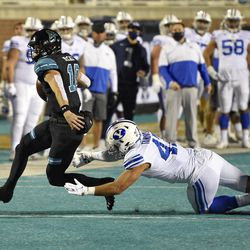 Coastal Carolina quarterback Grayson McCall (10) runs while defended by BYU's Pepe Tanuvasa during the first half of an NCAA college football game Saturday, Dec. 5, 2020, in Conway, S.C.