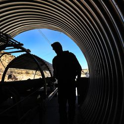 A worker walks by the reclaimed coal tunnel conveyor belt at the Bronco Utah Mine near Emery on Wednesday, March 29, 2017.