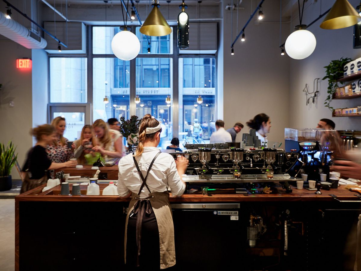 A barista stands behind the counter of a busy coffee shop, where customers line up to order and pay