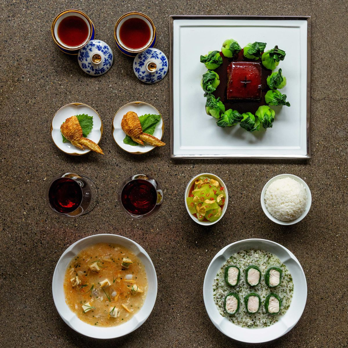 Eight Tables' Lunar New Year dishes arranged prettily on the table: stuffed chicken wings, DongPo pork surrounded by steamed bok choy, and more