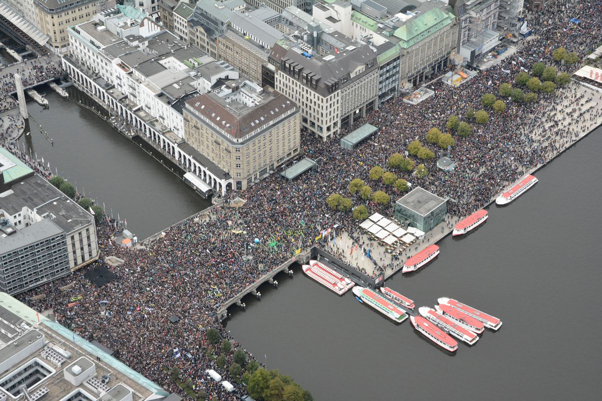 An aerial view of Hamburg, Germany, with people crowded onto the streets amid buildings, a canal, and boats in the water.