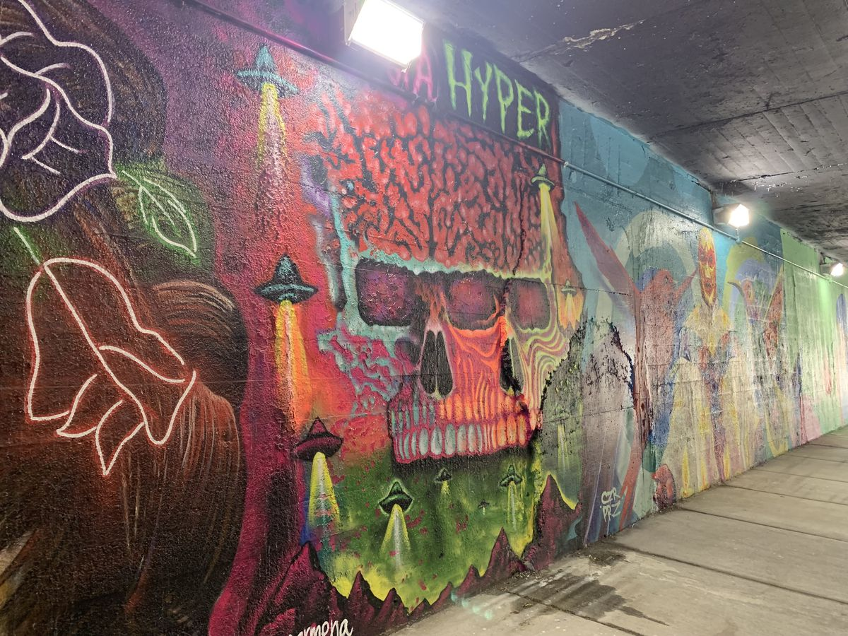 """This mural was done by Gage Park artist Mario Mena, who sometimes paints under the name """"Hyper Dimensional."""" """"I just tried to go for a little sci-fi look,"""" he says. """"I showed up and just figured it out. I like painting and feeling the moment."""" He says skulls are a """"recurring theme"""" in his work as in Mexican culture — in which death is not necessarily """"something to be afraid of."""""""