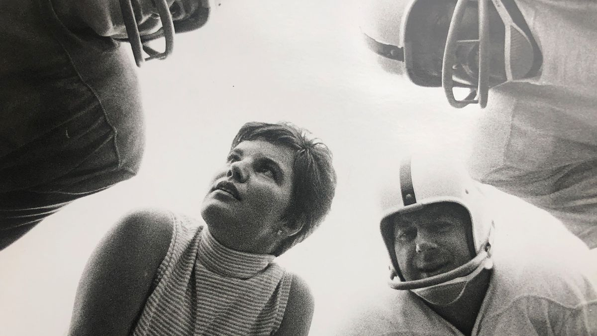 black and white photograph of Elinor Penna in a football huddle from the 1960's