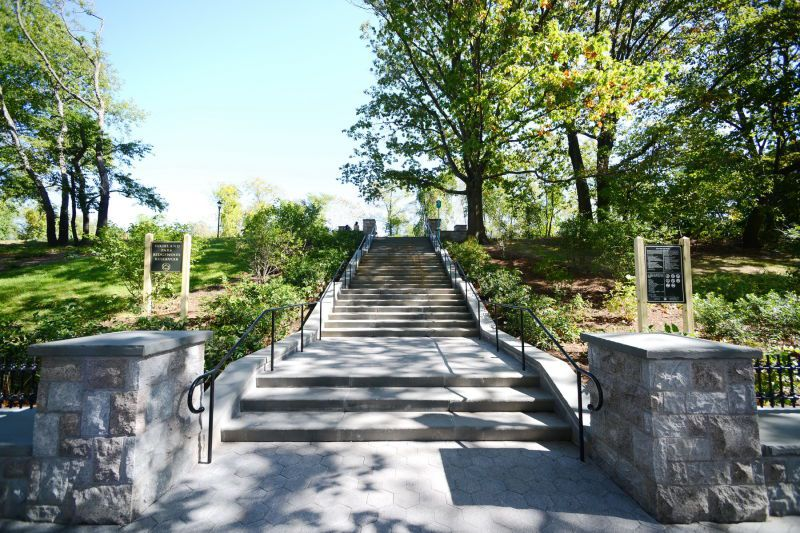 A park path with stairs. There are trees, plants, and grass on both sides of the path.