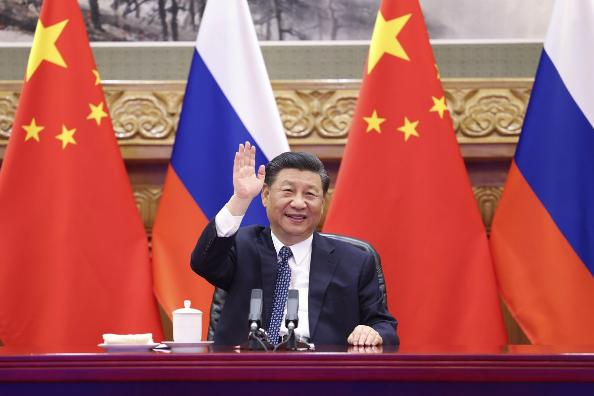 Chinese President Xi Jinping waves as he witnesses the ground-breaking ceremony of a bilateral nuclear energy cooperation project, Tianwan nuclear power plant and Xudapu nuclear power plant, via video link with his Russian counterpart Vladimir Putin from Beijing.