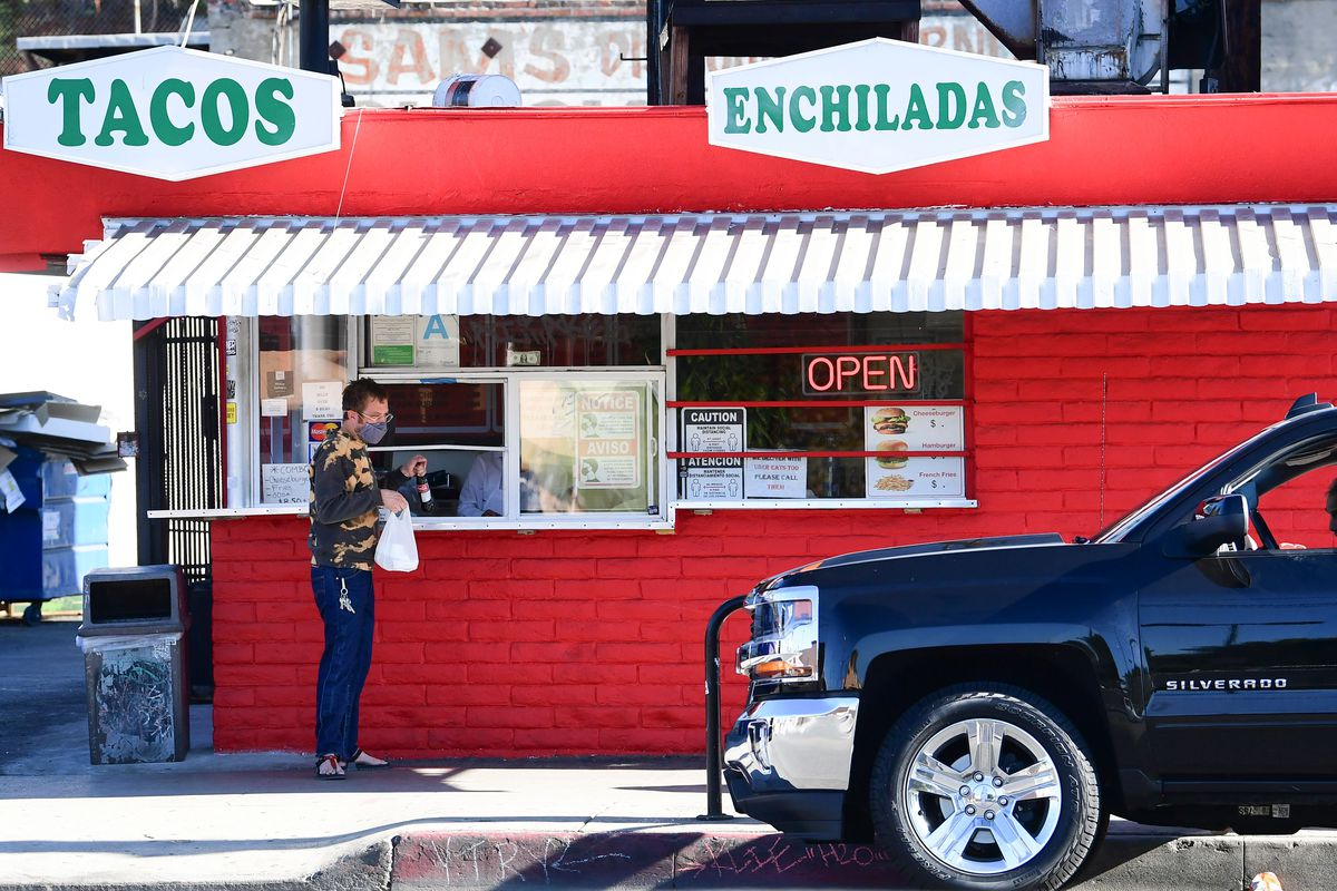 A customer receives his takeout order from a restaurant in Los Angeles, California on December 1, 2020.