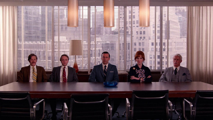 The five partners sit in the offices of McCann on Mad Men.