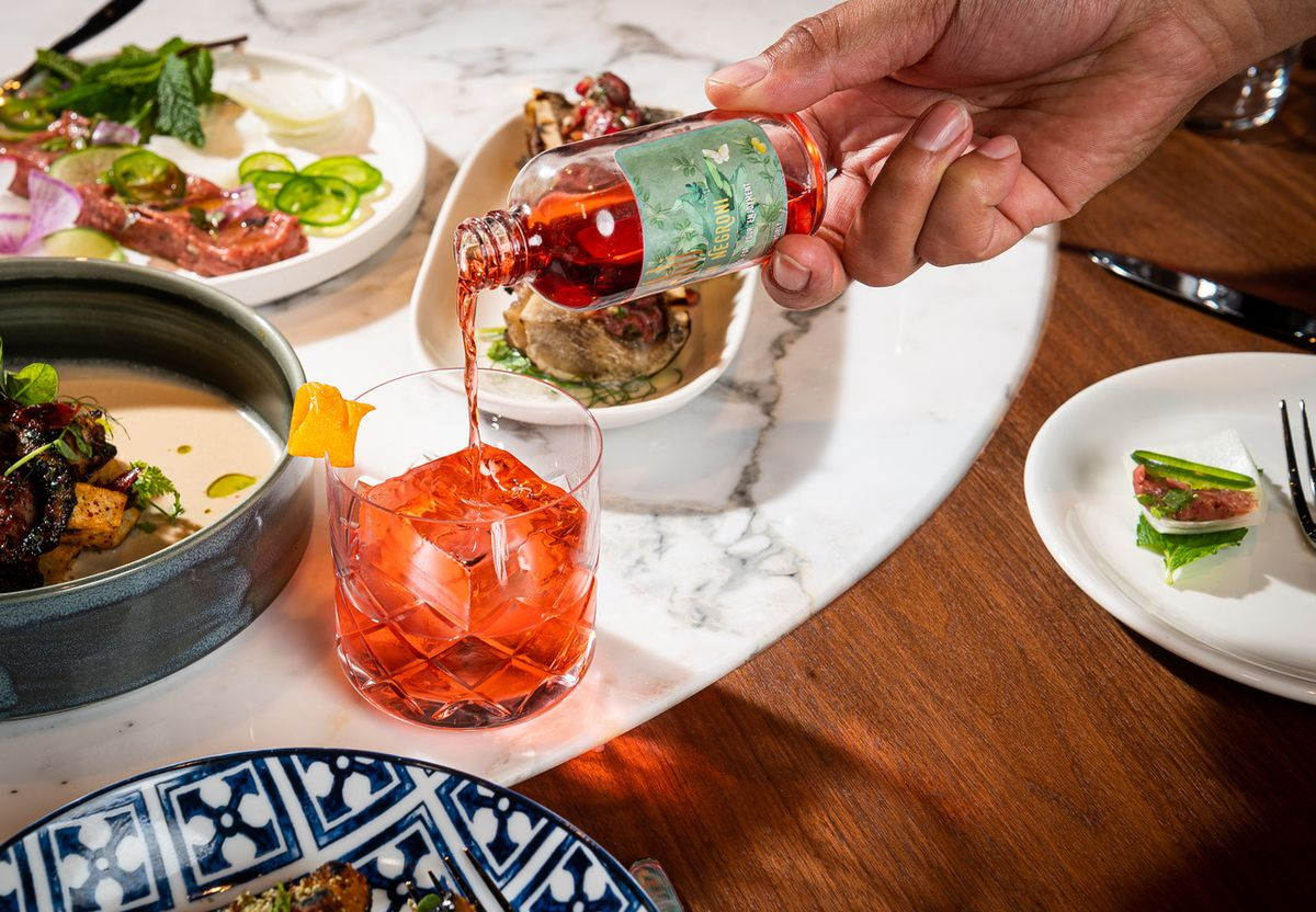 A saffron-infused negroni poured in a bottle tableside is surrounded by meze.