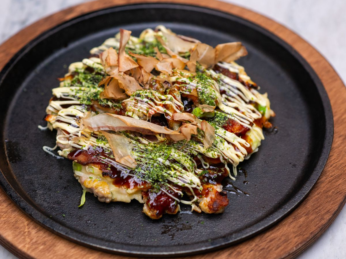 A round pancake covered in sauce and powdered seaweed on a round black plate