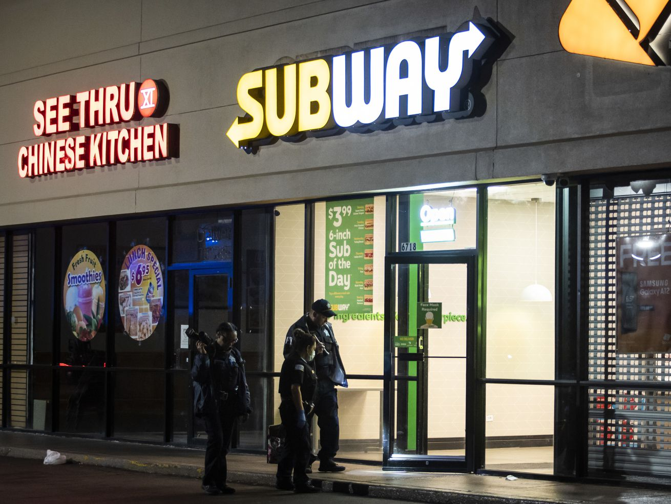 Chicago police investigate in a Subway at 6718 S. Stony Island Ave., where police said four teens were shot Sunday night as they stood in the parking lot of the Grand Crossing restaurant.