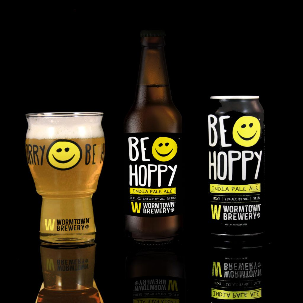 """A glass, bottle, and can labeled with a yellow cartoon happy face and the label """"be hoppy"""" sit side by side"""