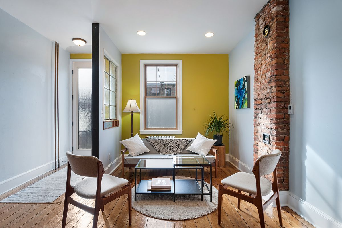 A sunny living room with pine floors, exposed brick chimney, and a yellow accent wall.