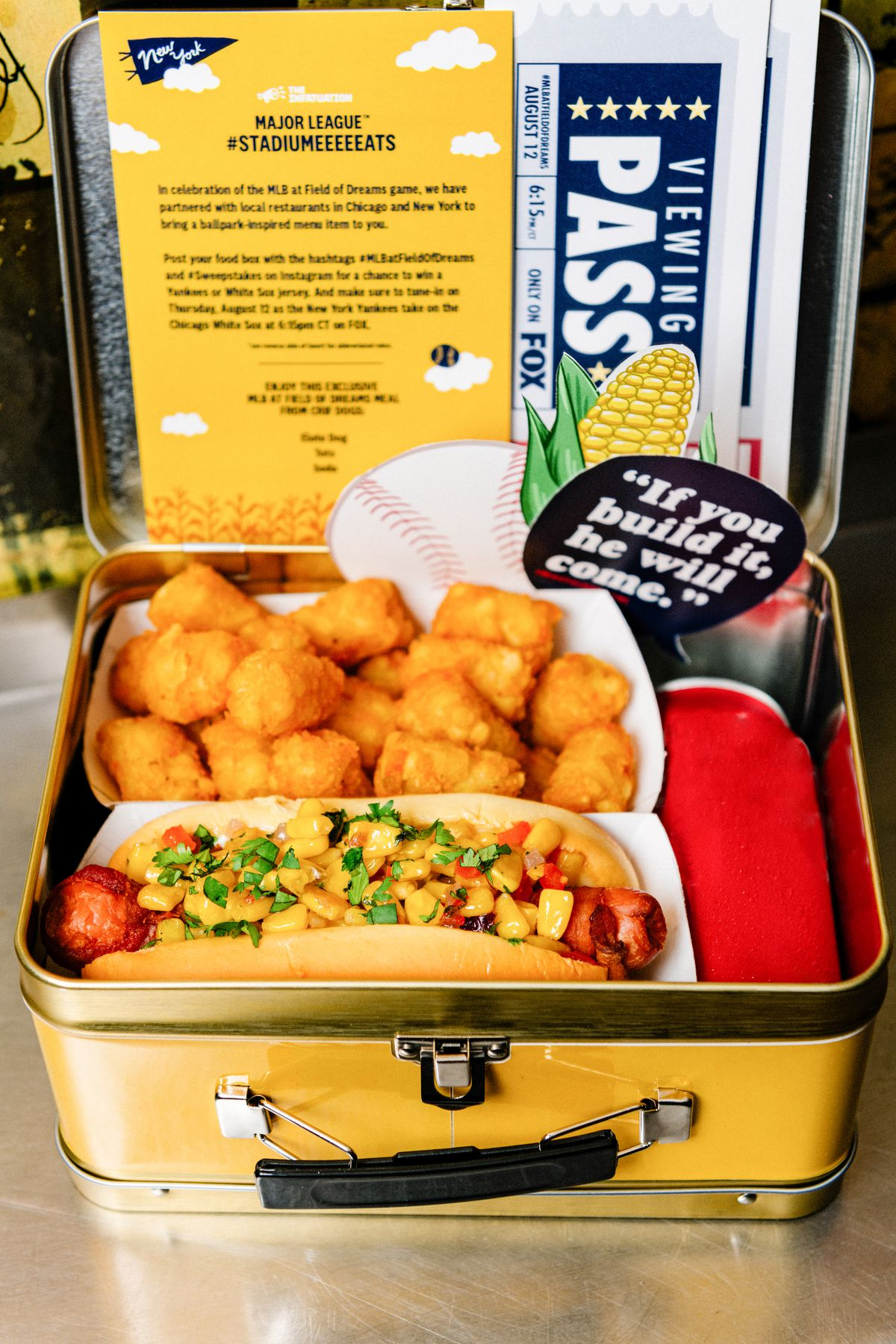 A lunch box will a hot dog, tater tots, and stickers.