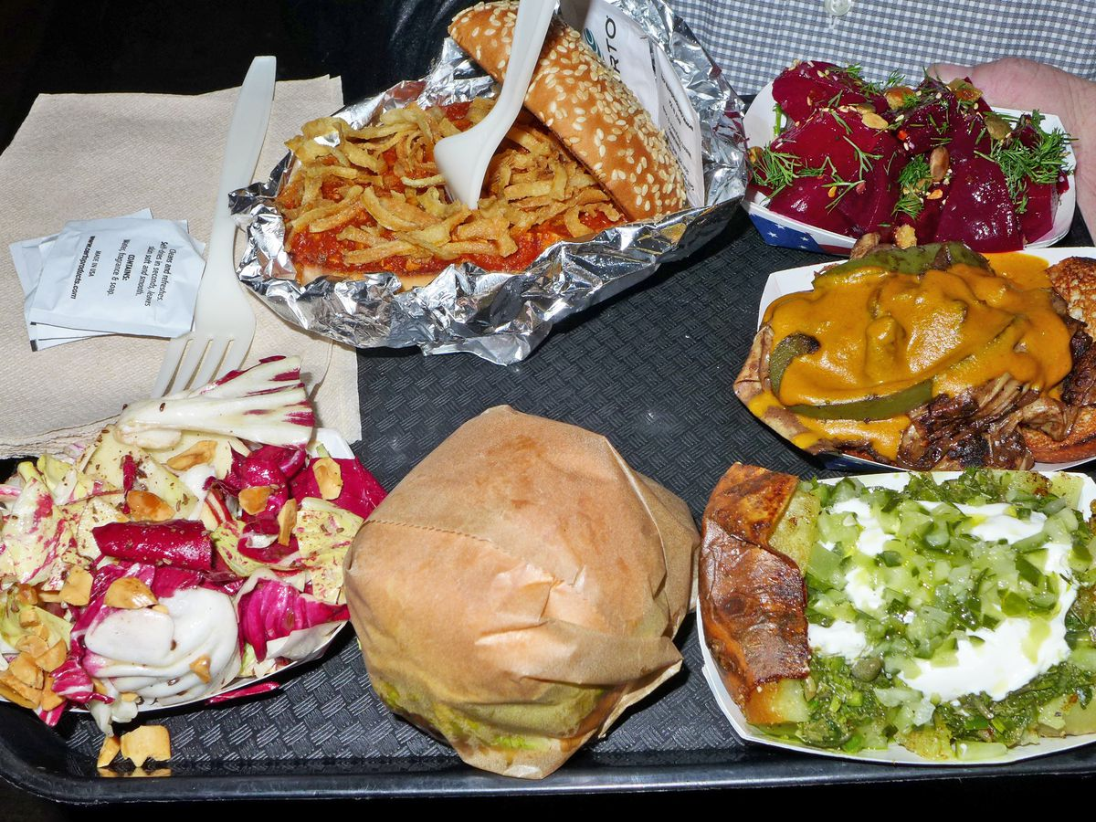 A selection of colorful vegetarian specialties on a black plastic try, including a sloppy joe, a tissue wrapped burger and four other things.
