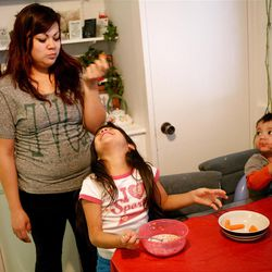 Adriana Carreon jokes around with her daughter Mariza, 6, and son Antonio, 2, at home in Taylorsville on Saturday, Feb. 9, 2013. Carreron's family was recently evicted, but they managed to land on their feet.