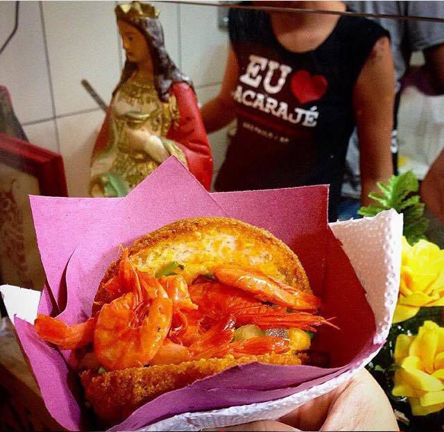 A fritter in colorful paper container is split open and filled with shrimp and fixings