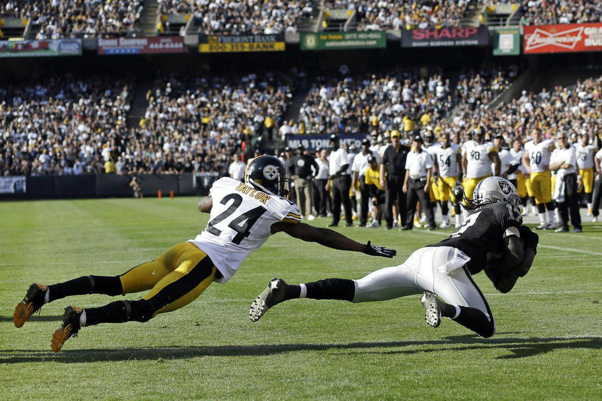 Oakland Raiders wide receiver Denarius Moore, right, scores a touchdown on a six-yard pass as Pittsburgh Steelers cornerback Ike Taylor, left, looks on during the fourth quarter of an NFL football game in Oakland, Calif., Sunday, Sept. 23, 2012. Oakland w