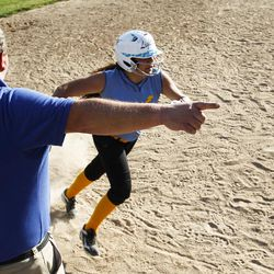 Brad Thomas, left, who has been coaching his daughter's accelerated softball team for the past five years, tells one of his players to run to home base during a scrimmage at Dewey Bluth Park in Sandy, Utah, Thursday, June 9, 2016.
