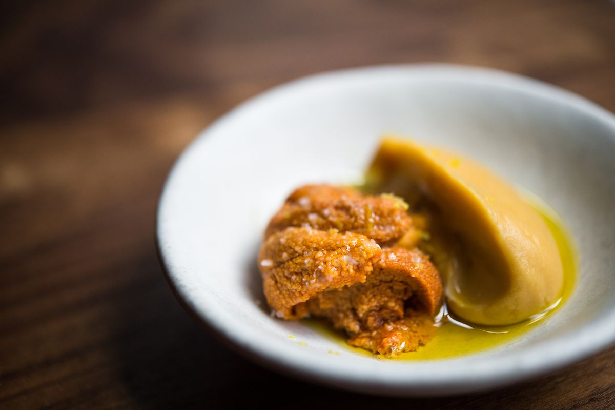 A few tongues of orange uni sit next to a yellow chickpea puree in a pool of green olive oil