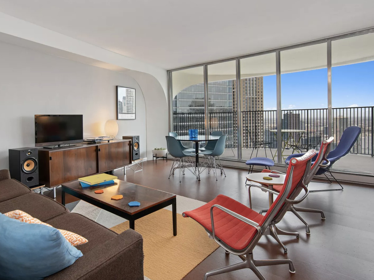 A condo in a high-rise tower with a curving balcony with a metal railing. The living room has midcentury furniture.